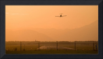 Light airplane landing at sunset on the summer sol