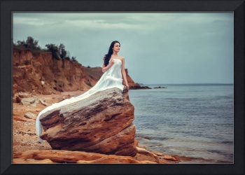 Attractive woman in white fabric on the rock