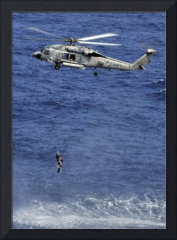 Search and rescue swimmers being hoisted into a he