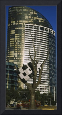 Sculpture of a cow on a tree in front of a buildi