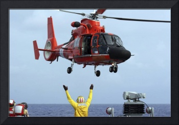 Boatswain Mate directs a HH 65A Dolphin aboard the
