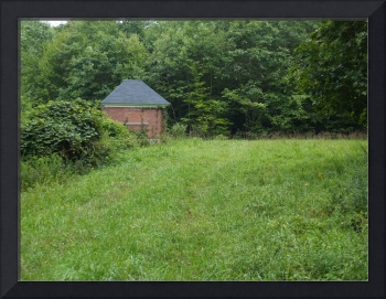 Small Building On The Edge Of A Grassy Hill