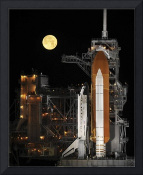 A nearly full Moon sets as Space Shuttle Discovery