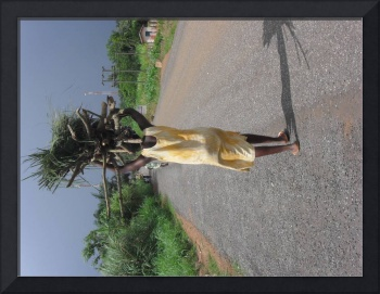 Woman carrying a heavy load of wood on head