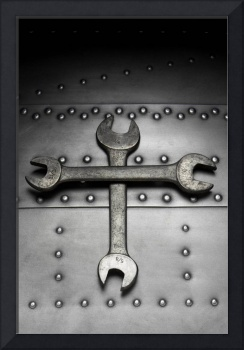 wrenches crossed on riveted steel background