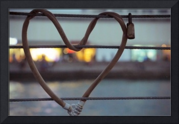 Heart-shaped padlock locked metal cables during tw