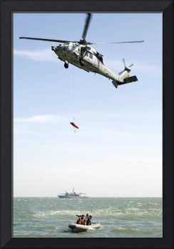 A litter is lowered from a SH-60B helicopter durin
