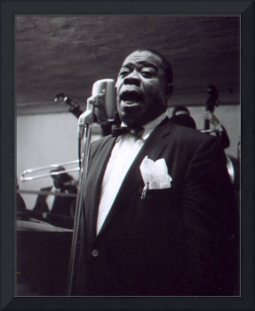 Louis Armstrong sings into the mic.