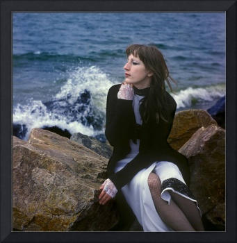 The romantic girl sits on stones on the seashore.