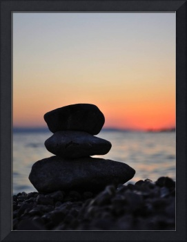Silhouette of three zen rocks on the beach