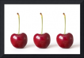 Three Red Cherries against a White Background