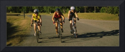 Three mid adult women cycling