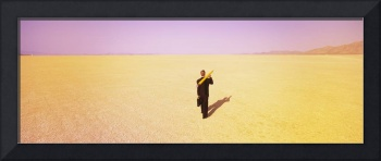 Businessman walking in a desert with a large penc