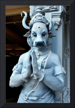 Blue Hindu statue with cow head praying