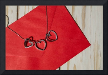 Silver heart pendants on a red envelope
