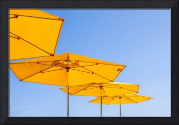 yellow sunshades and bright blue sky