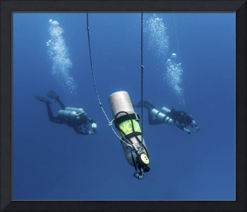 Technical divers ascend near a Nitrox stage bottle