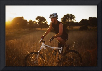 Man Riding His Bike Through Tall Grass At Sunset,