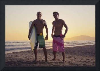 Two young men standing on the beach with a surfboa