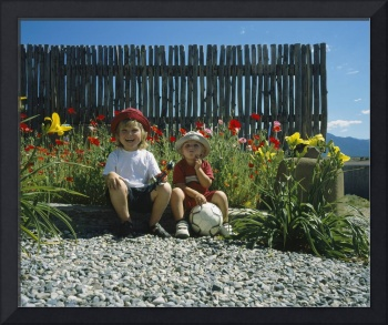 Two boys sitting in the backyard of a house