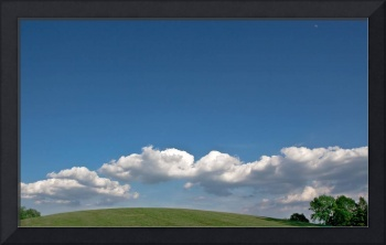 Grassy knoll with clouds, blue sky and moon