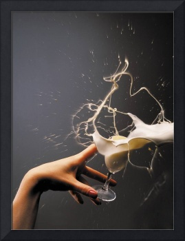 The hand with the flying glass of liqueur