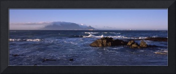Rocks in the sea with Table Mountain in the backg