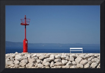 Red lighthouse and white bench in stones