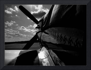 WWII fighter plane with clouds in background