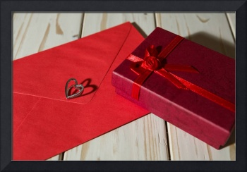 Silver heart pendant on red envelope and gift box