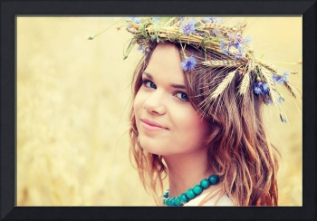 Beautiful young girl in summer field with grain an