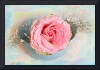 A single pink rose placed in a blue salad bowl