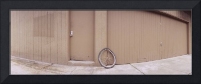 Bent bicycle tire leaning against a wall near a c