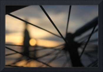 sunset thru spokes of bicycle
