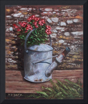 Old watering can with flowers by stone wall