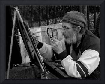 Artist painting through a magnifying glass