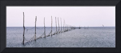 Net tied to wooden posts in the sea