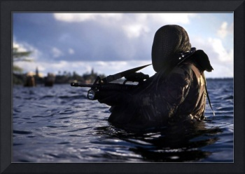 A Navy SEAL emerges from underwater during a train
