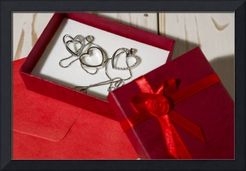 Silver heart pendants in a red gift box