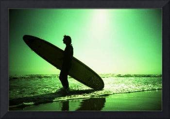 Surfer carrying surfboard in surreal silhouette in