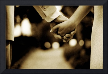 Bride and groom holding hands sepia toned photo