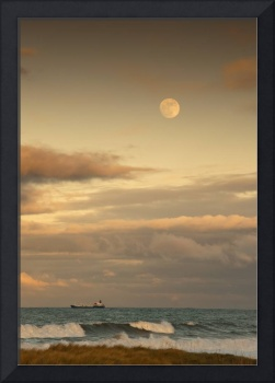 A Cargo Ship On The Ocean With The Moon In The Sky