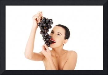 Beautiful sensual brunette eating grapes, isolated
