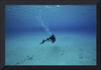 A diver on a scooter explores the clear blue water