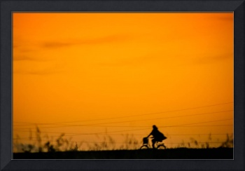 Girl with bycicle on countryside road.