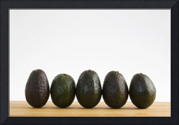 A Row Of Avocados Standing Upright On A Wooden Boa
