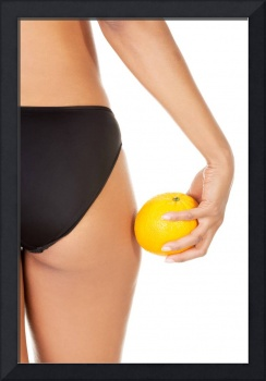 A girl holding an orange next to the buttocks, iso