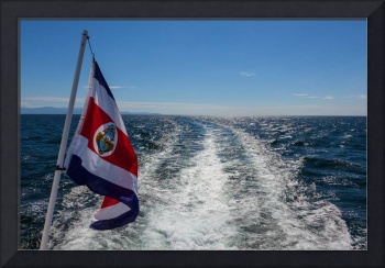 the flag of Costa Rica flying behind a boat