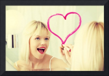 Young beautiful woman drawing big heart on mirror