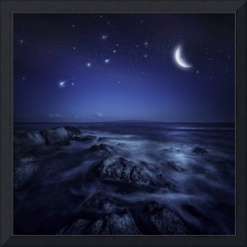 Rising moon over ocean and boulders against starry